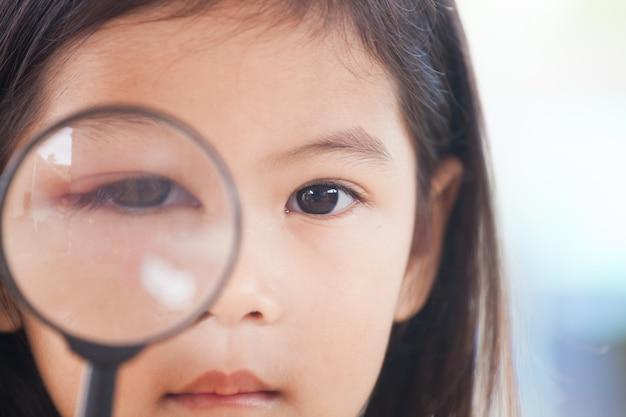 Il primo piano dell'occhio asiatico della ragazza del bambino gonfia dal virus dei batteri che guarda attraverso una lente d'ingrandimento