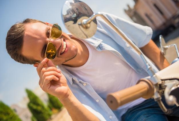 Il primo piano dell'uomo allegro in occhiali da sole sta sedendosi sul motorino