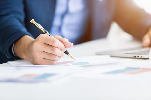 Il primo piano dell'uomo d'affari che lavora con prende nota della carta di affari e della tastiera di battitura a mano del computer portatile in ufficio