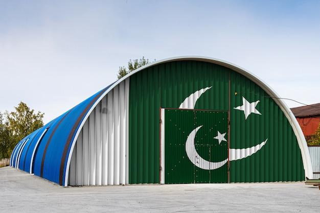 Il primo piano della bandiera nazionale del pakistan ha dipinto sulla parete del metallo di un grande magazzino il territorio chiuso contro il cielo blu.