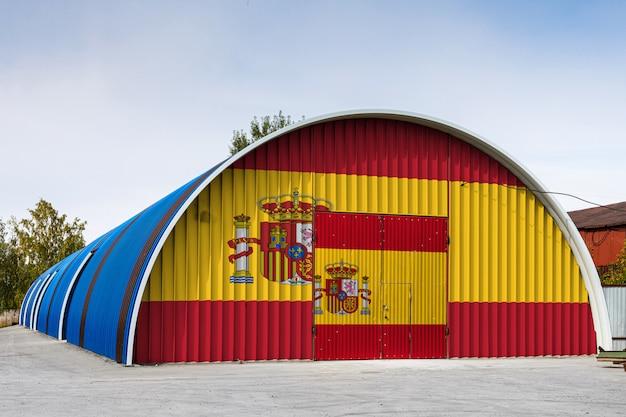Il primo piano della bandiera nazionale della spagna ha dipinto sulla parete del metallo di un grande magazzino il territorio chiuso contro cielo blu. il concetto di stoccaggio delle merci, ingresso in un'area chiusa, logistica