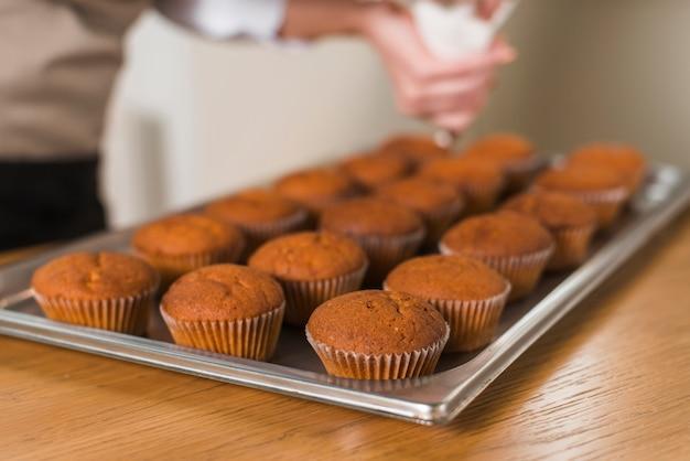 Il primo piano della donna che decora il fresco cuoce i muffin con crema sul vassoio