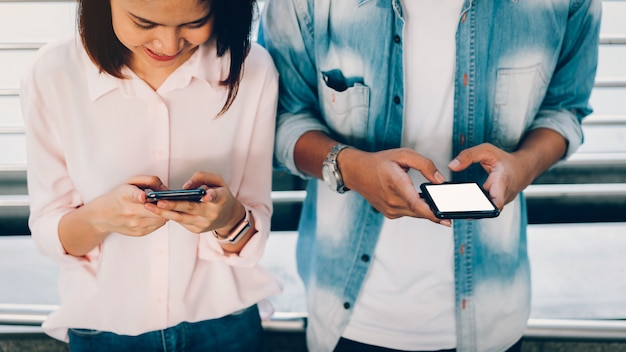 Il primo piano della donna che tiene uno smartphone, deride su dello schermo in bianco. usando il cellulare sullo stile di vita. tecnologia per il concetto di comunicazione.