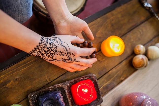 Il primo piano della donna con mehndi arabo sulla sua mano tiene le perle sullo scrittorio di legno