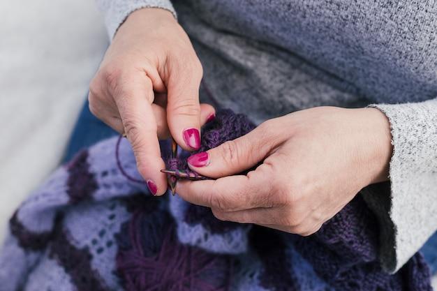 Il primo piano della donna lavora a maglia i vestiti di lana con i ferri da maglia