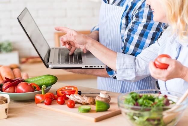 Il primo piano della donna senior che indica al computer portatile tiene da suo marito mentre prepara l'insalata di verdure