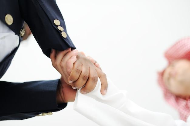 Il primo piano della gente di affari che stringe le mani sopra un affare