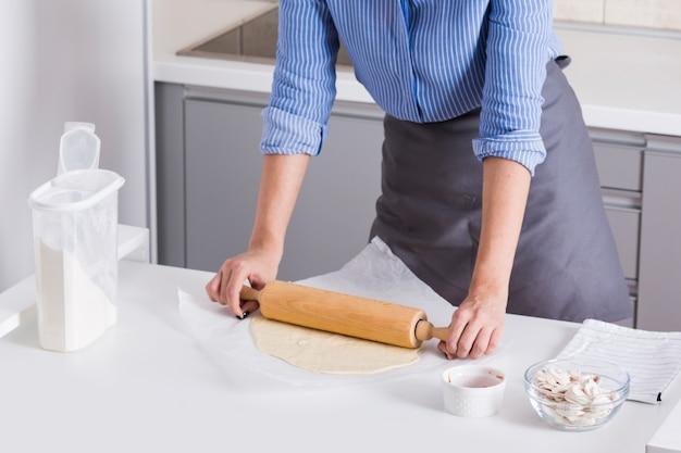 Il primo piano della giovane donna ha appiattito la pasta con il matterello sulla tavola bianca