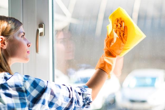 Il primo piano della giovane donna pulisce la finestra con il tovagliolo giallo