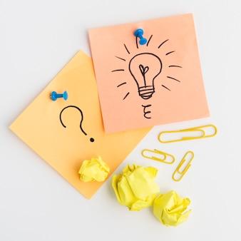 Il primo piano della lampadina tirata e del punto interrogativo firmano sulla nota adesiva allegata con la puntina da disegno blu contro fondo bianco