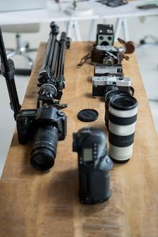 Il primo piano della macchina fotografica digitale e del treppiede stanno sulla tavola
