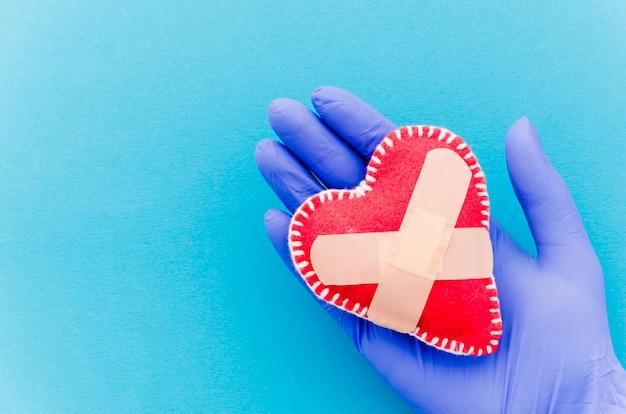 Il primo piano della mano che indossa i guanti chirurgici che tengono il cuore ha cucito il cuore del tessuto cucito con le fasciature attraversate sul contesto blu