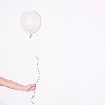 Il primo piano della mano che tiene il singolo pallone bianco con variopinto spruzza dentro contro contesto bianco