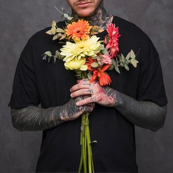 Il primo piano della mano del giovane tatuato che tiene il mazzo floreale a disposizione contro la parete grigia