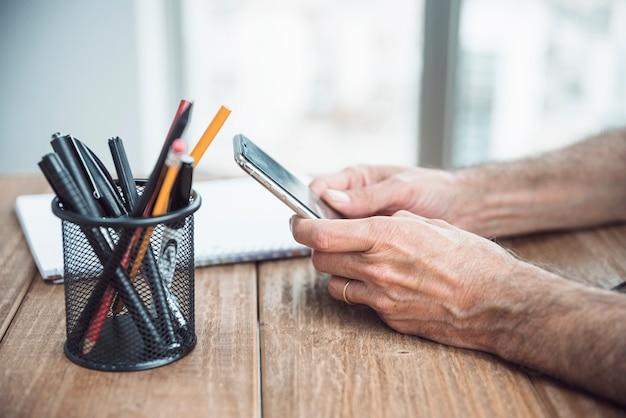 Il primo piano della mano dell'uomo che tiene lo smart phone a disposizione sopra lo scrittorio di legno
