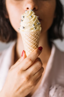 Il primo piano della mano della donna che mangia il cono gelato con l'argento spruzza le palle