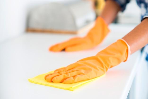 Il primo piano della mano della donna pulisce la tavola bianca con il tovagliolo giallo