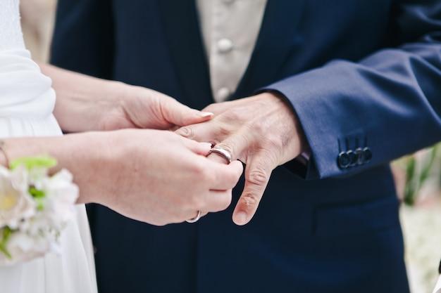 Il primo piano della mano della sposa mette un anello nuziale sul dito degli sposi, la cerimonia sulla strada