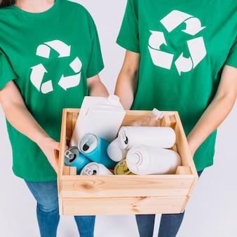 Il primo piano della mano di due donne che tiene la scatola di legno con ricicla gli oggetti