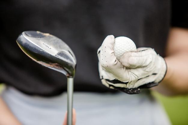 Il primo piano della mano di un giocatore di golf femminile che tiene una palla da golf e una testa del club
