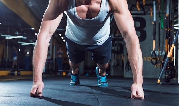 Il primo piano della mano di un uomo muscolare che fa spinge aumenta in palestra