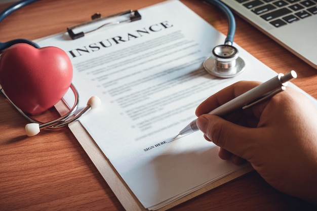 Il primo piano della mano sta firmando i documenti di contratto di polizza di contratto. firma del contratto di assicurazione.