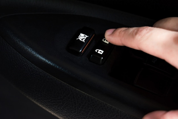 Il primo piano della mano sta premendo il pulsante del finestrino elettrico in macchina.