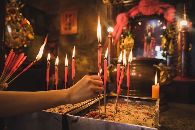 Il primo piano della mano tiene le candele rosse nel vecchio vaso di incenso.