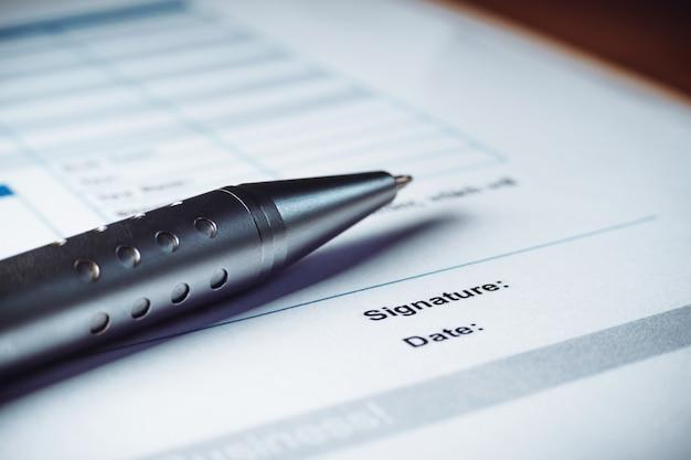 Il primo piano della penna d'argento sta firmando i documenti di accordo di politica dei contratti. firma del contratto legale.