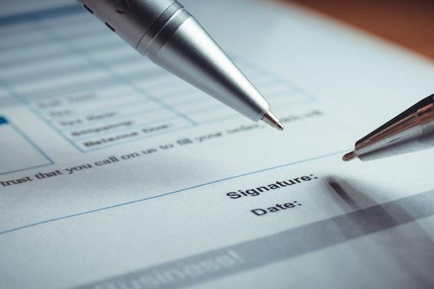 Il primo piano della penna d'argento sta firmando i documenti di accordo di polizza di contratto. firma del contratto legale.