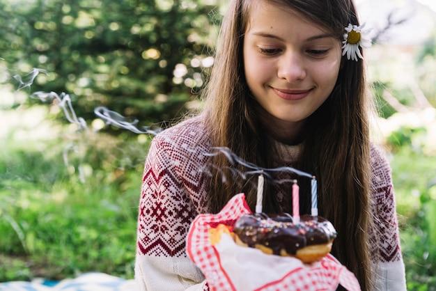 Il primo piano della ragazza sorridente che esamina estingue le candele sopra la ciambella
