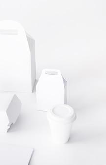 Il primo piano della tazza di smaltimento e del pacchetto dell'alimento deride su su fondo bianco