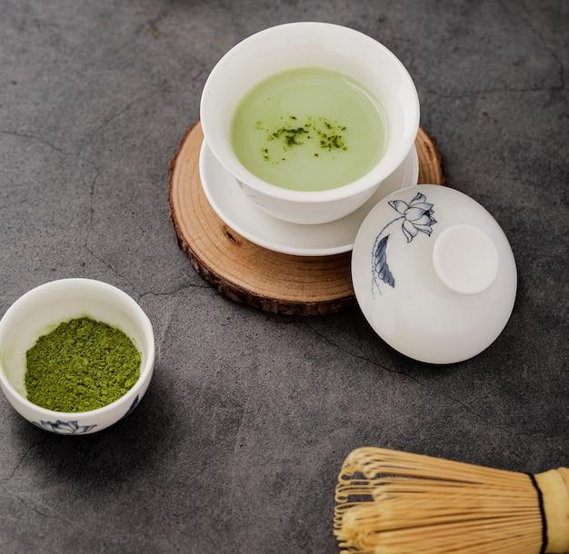Il primo piano della tazza di tè di matcha con bambù sbatte