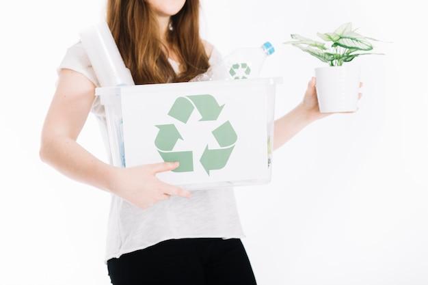 Il primo piano della tenuta della donna ricicla la cassa e la pianta in vaso