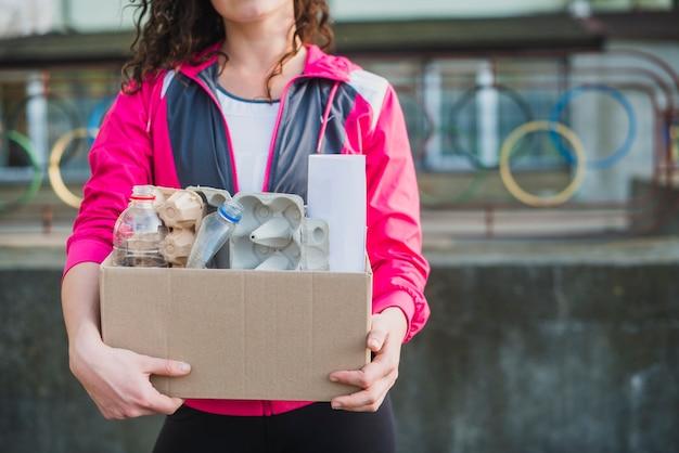 Il primo piano della tenuta della donna ricicla la scatola di cartone