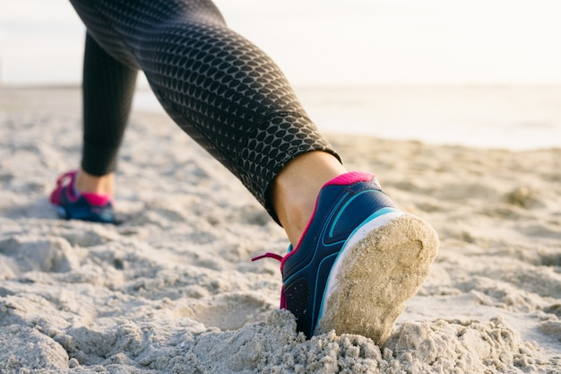 Il primo piano delle gambe femminili in calzamaglia e scarpe da tennis durante l'esercizio mattutino sulla spiaggia