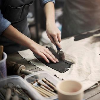 Il primo piano delle mani delle terraglie che taglia l'argilla con lo strumento