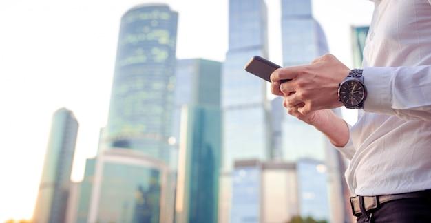 Il primo piano delle mani maschii sta tenendo il cellulare all'aperto sulla via. uomo che usando smartphone mobile.
