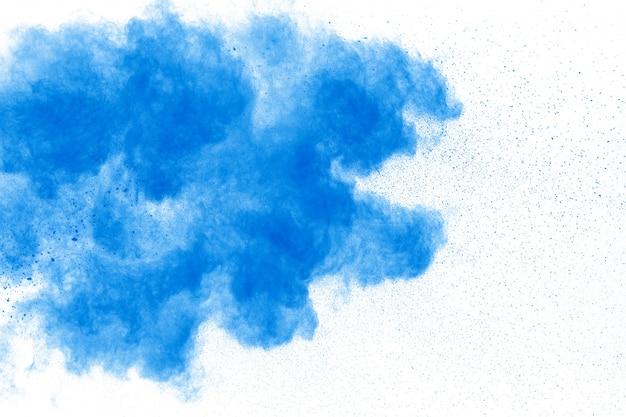 Il primo piano delle particelle blu della polvere spruzza su fondo.