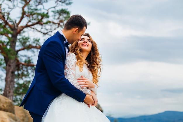 Il primo piano dello sposo abbraccia la sposa dalla parte posteriore