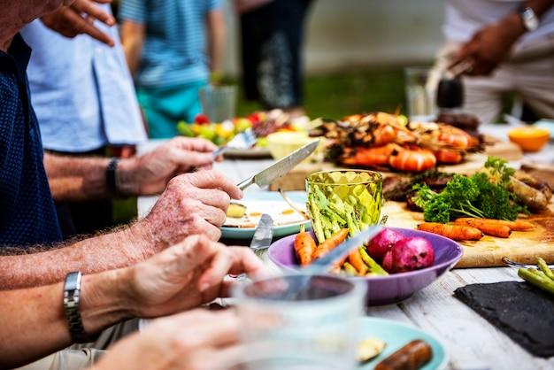 Il primo piano di diversa gente che gode del barbecue fa festa insieme