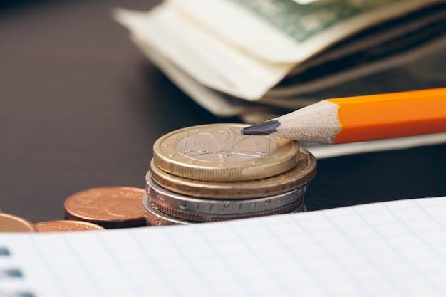 Il primo piano di documenti contabili con monete di denaro
