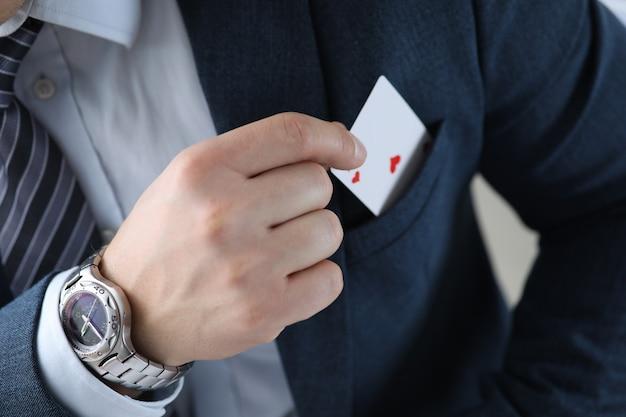Il primo piano di equipaggia la mano che tira la carta dell'asso dalla tasca del vestito