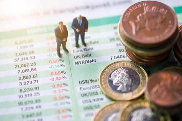 Il primo piano di impilamento delle monete di sterlina con l'uomo di affari sul tasso di cambio del giornale
