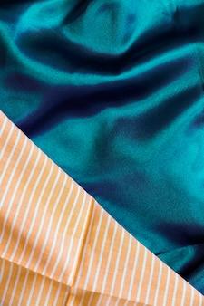Il primo piano di tessuto di seta verde e strisce arancioni modellano il materiale del tessuto