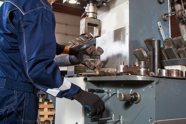 Il primo piano di un meccanico maschio in uniforme blu lavora su una saldatrice automatica per la riparazione di alberi cardanici per la riparazione di auto e camion
