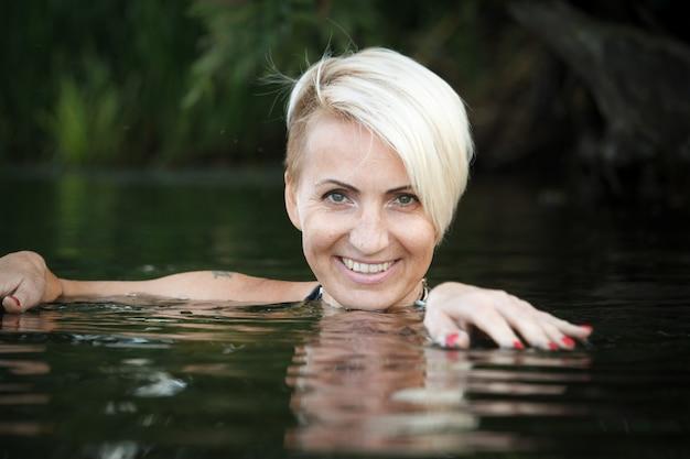 Il primo piano di una donna bionda di mezza età nuota nel fiume.