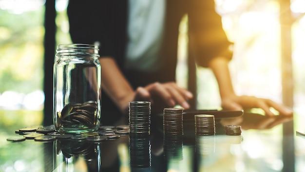 Il primo piano di una donna di affari che calcola con le monete impila e un barattolo di vetro dei soldi per il concetto di risparmio e finanziario