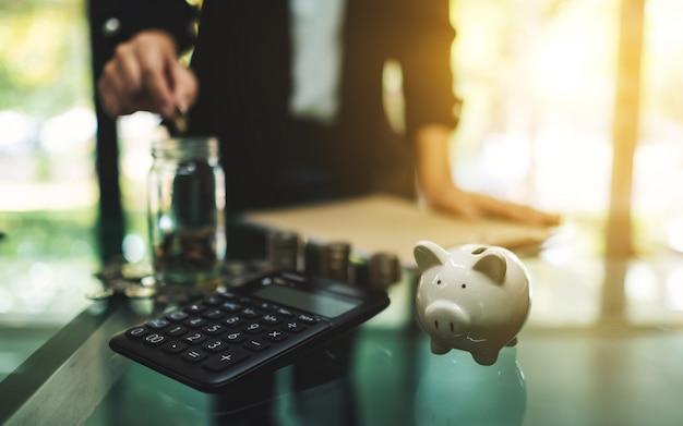 Il primo piano di una donna di affari che mette le monete in un barattolo di vetro con il calcolatore, il porcellino salvadanaio e le monete impilano sulla tavola per il concetto di risparmio e finanziario