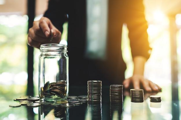 Il primo piano di una donna di affari che mette le monete in un barattolo di vetro con la moneta impila sulla tavola per il risparmio dei soldi e del concetto finanziario